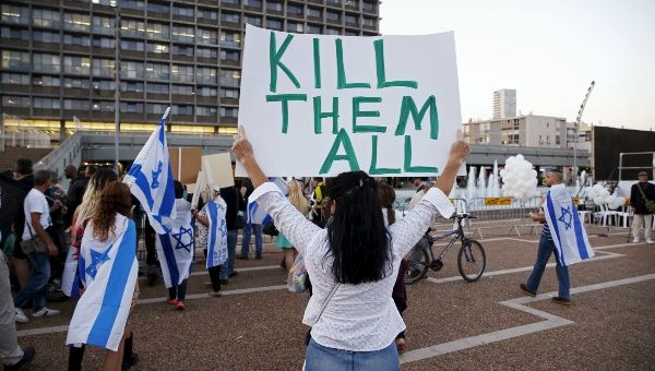 A supporter the Israeli soldier charged with manslaughter holds a placard calling for violence in Tel Aviv, Israel April 19, 2016.
