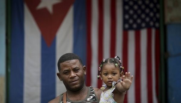 Yoendry Gainsa, 35, a bricklayer, holds his daughter while posing for a photograph in front of the Cuban and U.S. flags in Havana.