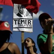Members of social movements hold signs during a protest against Brazil
