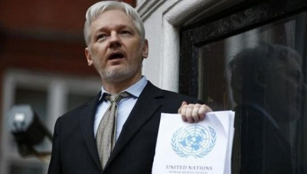 WikiLeaks founder Julian Assange holds a copy of a U.N. ruling as he makes a speech from the balcony of the Ecuadorian Embassy, in central London, Britain Feb. 5, 2016.