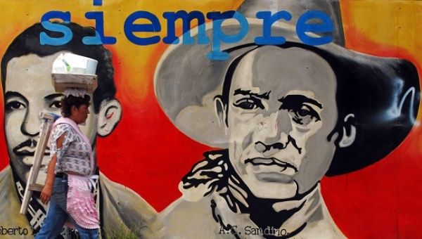 A woman walks in front of a mural of Augusto César Sandino.