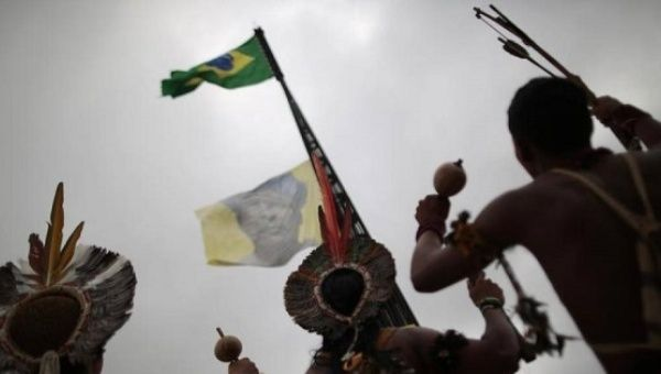 Indigenous from various parts of Brazil watch the hoisting of a flag with an image of Indian leader Arnaldo Kaba of the village Mundurukoe, during a demonstration to defend the territorial rights of the Indigenous population against the government, agribusiness and large mining and energy companies.