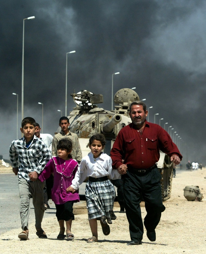 A British Warrior tank bears down on a family in the major southern city of Basra a few days after crossing the Iraqi frontier from Kuwait on March 28, 2003.