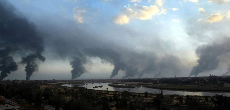 Palls of black smoke from raging oil fires billow over Baghdad, on March 27, 2003. The oil-filled trenches were set off by Iraqis to try and block the visibility of U.S.-led coalition warplanes and missiles.