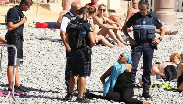 Woman on Nice beach being forced to remove her burkini by armed police, Aug. 23, 2016.