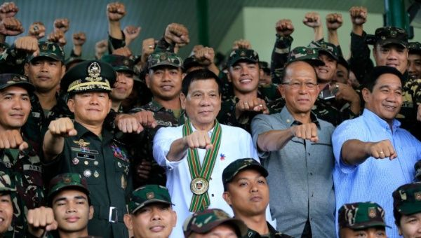 Philippines President Rodrigo Duterte (C) clenches fist with members of the Philippine Army during a visit to the army headquarters.
