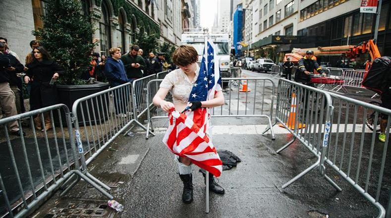 A pocos metros de la torre Trump, una mujer aprovechaba la presencia de cámaras para escenificar la quema de la bandera de las barras y estrellas.