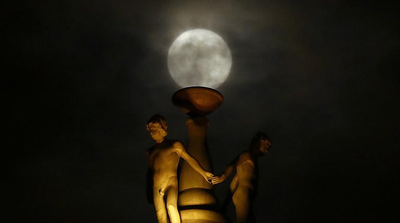 La luna está parcialmente cubierta por las nubes, ya que se eleva detrás de una estatua en la parte superior de la antigua ópera en el centro de Frankfurt, Alemania.