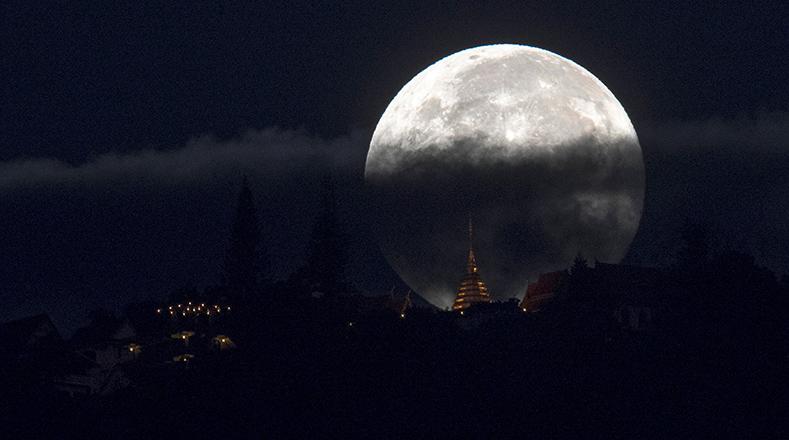Cubierta parcialmente por las nubes, la superluna ya se ve  detrás de Wat Phrathat Doi Suthep en la capital del norte de Chiang Mai, Tailandia.