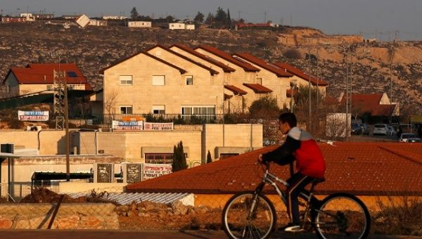 A boy rides his bicycle past houses in the Israeli settlements of Ofra, in the occupied West Bank, Feb. 6, 2017.