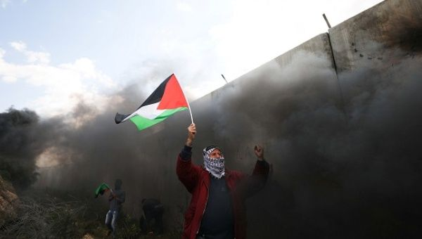 Protester holds a Palestinian flag during clashes with Israeli troops at a protest marking in the West Bank village of Bilin near Ramallah.