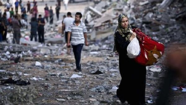 A Palestinian woman takes belongings from her partially destroyed home across the street from where a building was targeted by Israeli airstrikes, Aug. 26, 2014.