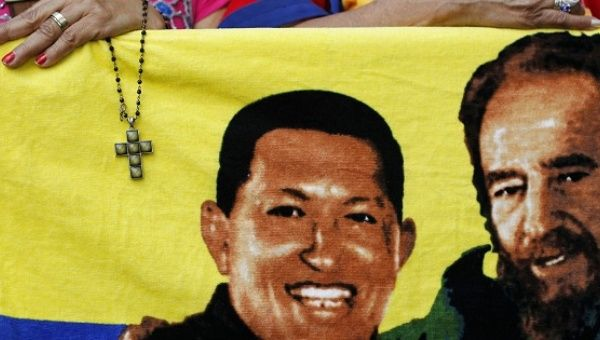 A supporter holds a crucifix next to a flag of Hugo Chavez (L) with Fidel Castro (R) in Caracas Jan. 5, 2013
