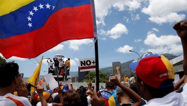 Opposition supporters holding a Venezuelan flag protest against Venezuela