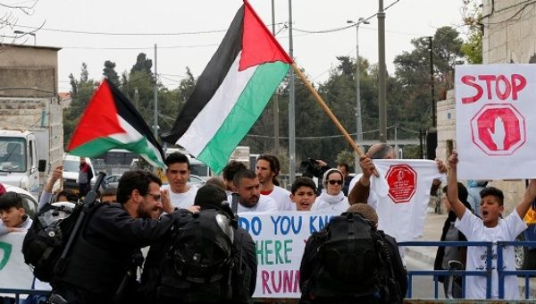 Demonstrators hold Palestinian flags during a protest against the annual Jerusalem Marathon outside Jerusalem