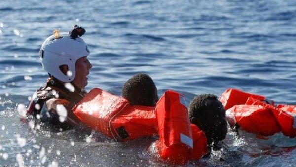 A rescue swimmer holds onto refugees frantically trying to stay afloat after falling off their rubber dinghy during a rescue operation off the coast of Zawiya in Libya, April 14, 2017.