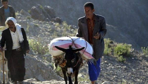 A Yemeni man uses a donkey to transport foodstuff on a mountainous road on route to the city of Taiz.