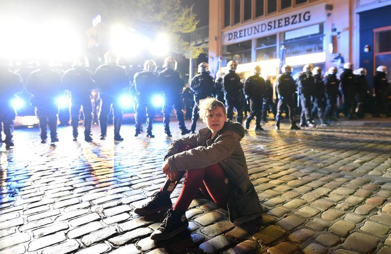 A man sits on the ground as German riot police stands guard during May Day demonstrations in Hamburg, Germany, May 1, 2017.