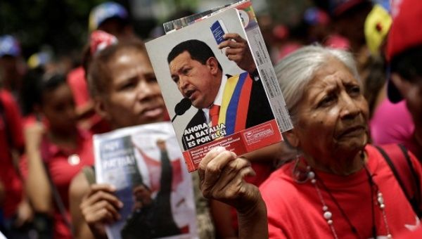 Supporters of President Nicolas Maduro rally to support him while carrying pictures of late Venezuela