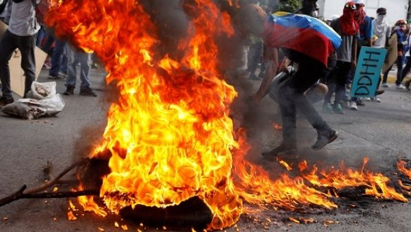 Opposition supporters set up a burning barricade at a rally against Venezuela