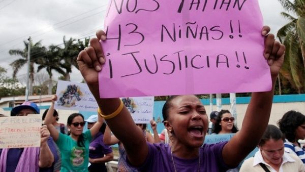 """An activist holds a sign that reads """" We are missing 43 girls. Justice"""" during a protest outside of Guatemala"""