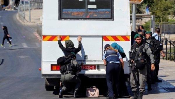 Israeli border police officers perform a frisk search of Palestinian women near Damascus Gate in Jerusalem