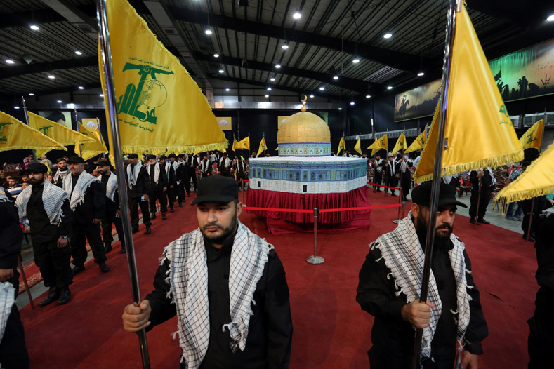 Hezbollah members carry Hezbollah flags as they stand in front of a replica of the Dome of the Rock during a rally marking Al-Quds day in Beirut