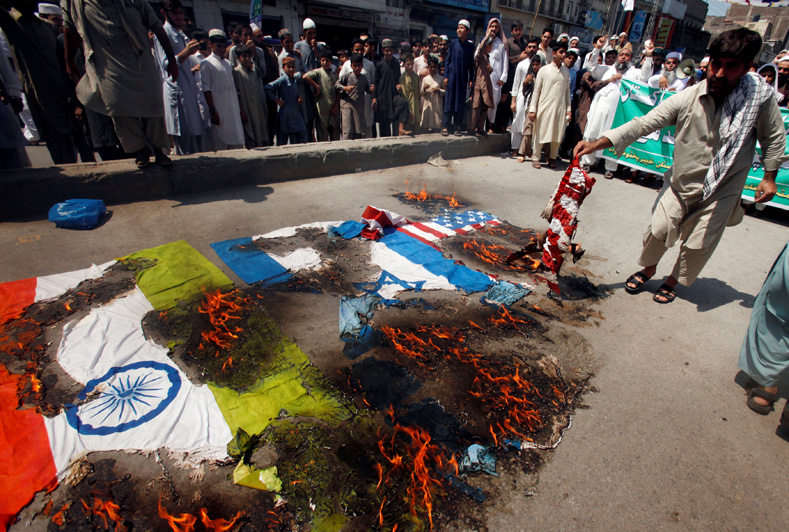Protesters burn American, Israeli and Indian flags during a demonstration marking the annual al-Quds Day, or Jerusalem Day, during the Muslim holy month of Ramadan in Peshawar, Pakistan June 23, 2017.