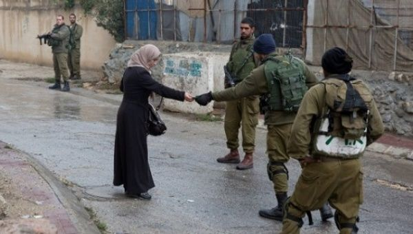Israeli soldiers check the ID of a Palestinian woman in the Tel Rumeida neighborhood of Hebron, West Bank.