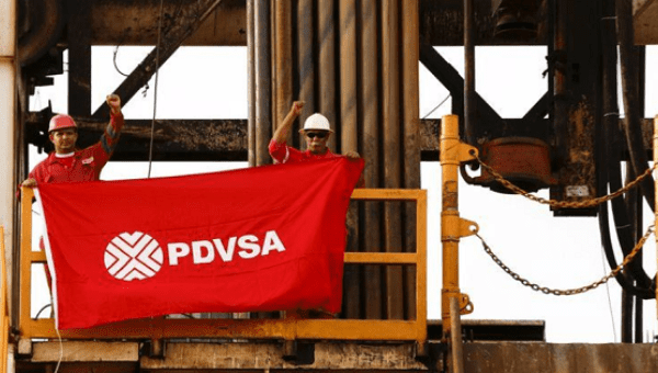 Oilfield workers hold a flag with the corporate logo of Venezuela