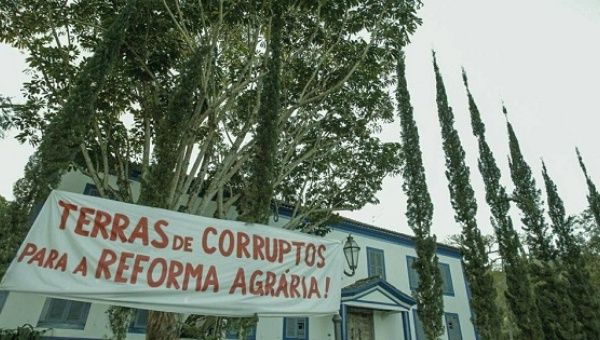"""A sign outside the farm reads, """"Lands of the corrupt for the agrarian reform,"""" in Sao Paulo."""