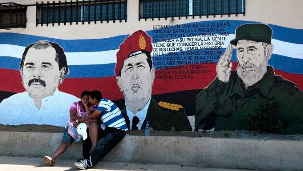 A couple sits in front of a mural depicting Nicaragua's President Daniel Ortega, Venezuela's Hugo Chavez, and Cuba's Fidel Castro in Managua.