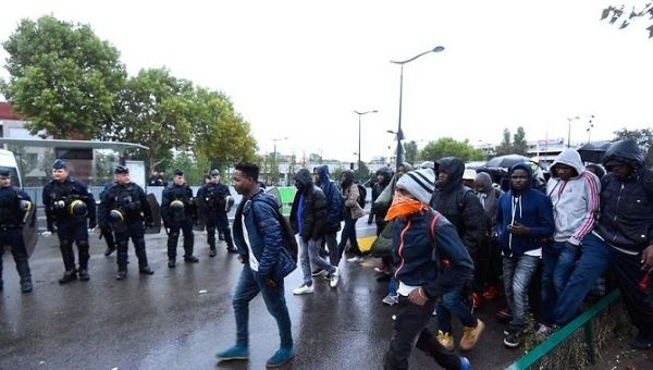 Paris Police Forces Evict Nearly 2 000 Asylum Seekers From Camp     French police look on as migrants walk towards waiting buses as they are  evacuated from a
