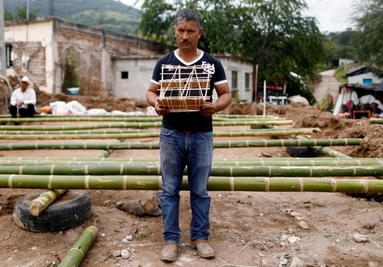 Hector Guzman, 48, a farm worker and representative of the Municipal President in San Jose Platanar, hold the model of a new house for his father.