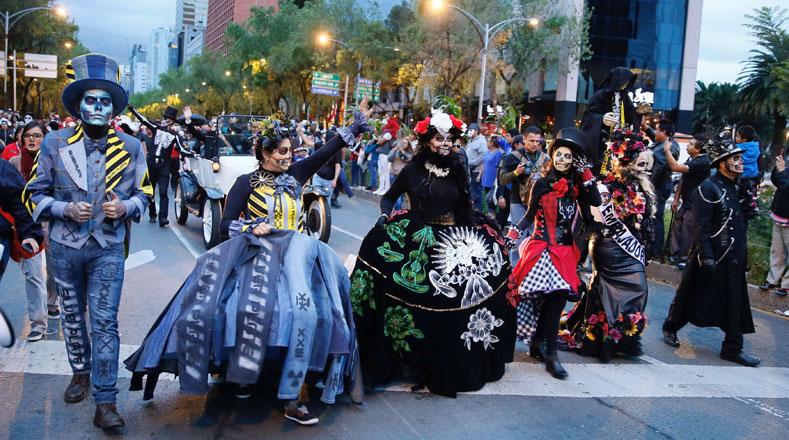 """La """"catrina"""" estuvo representada por varias mujeres mexicanas que pintaron sus rostros y usaron vestidos de época; hombres con disfraces de esqueletos y niñas con trajes tradicionales."""