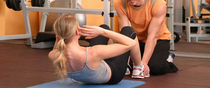 Woman doing sit ups assisted by a trainer