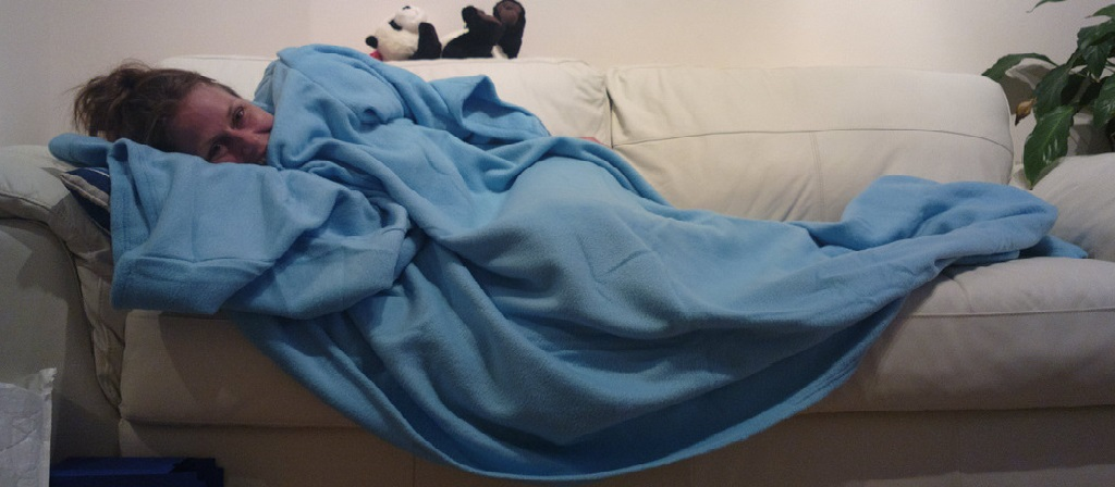 laying down on the sofa with blue blanket