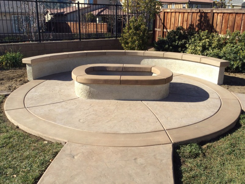 Oval fire pit with sitting wall and colored concrete in Mennifee McCabe's Landscape Construction
