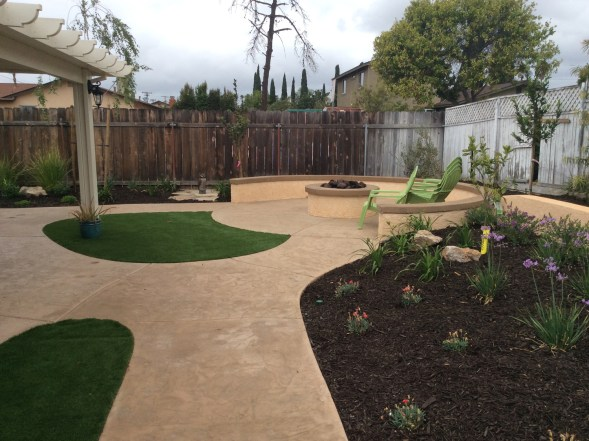 Fire pit with seating wall, concrete and artificial turf in Oceanside McCabe's Landscape Construction