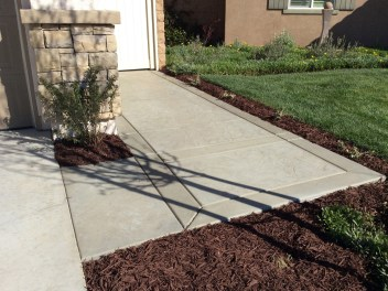 Grey concrete sidewalk with borders Oval fire pit with sitting wall and colored concrete in Winchester McCabe's Landscape Construction