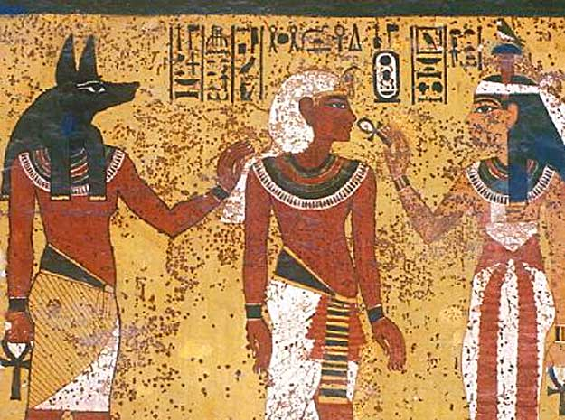 Front Wall, Right Part, Tutankhamun's Burial Chamber - god Anubis, on left, leads Tutankhamun before goddess Hathor, on right, who gives the breath of life to King Tut through the nostrils with the ankh.  The symbols of life, prosperity, time and eternity are directly over Tut's head.