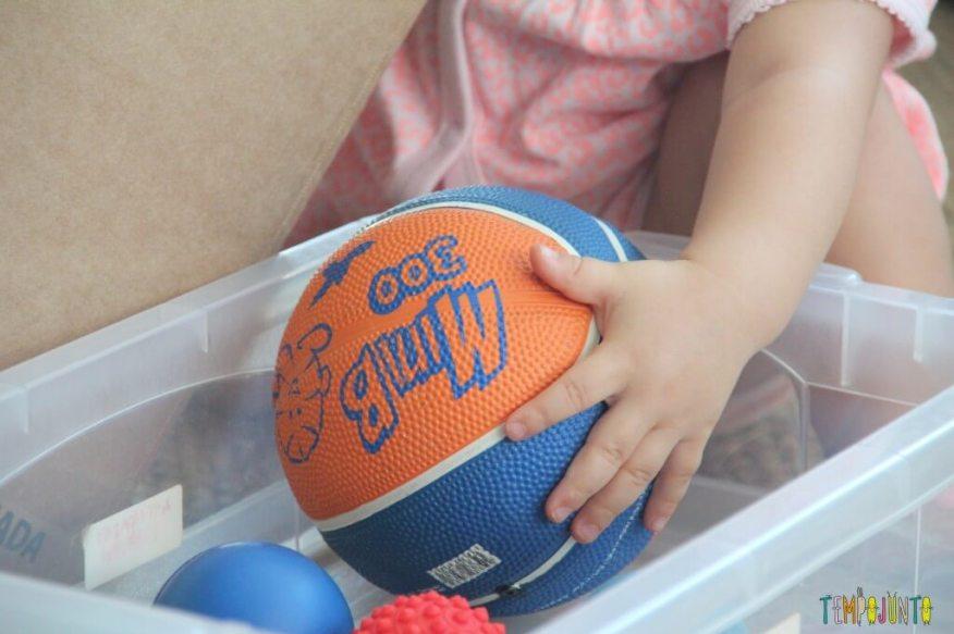 Brincadeira para bebês com bolas e caixas - mão da gabi com a bola