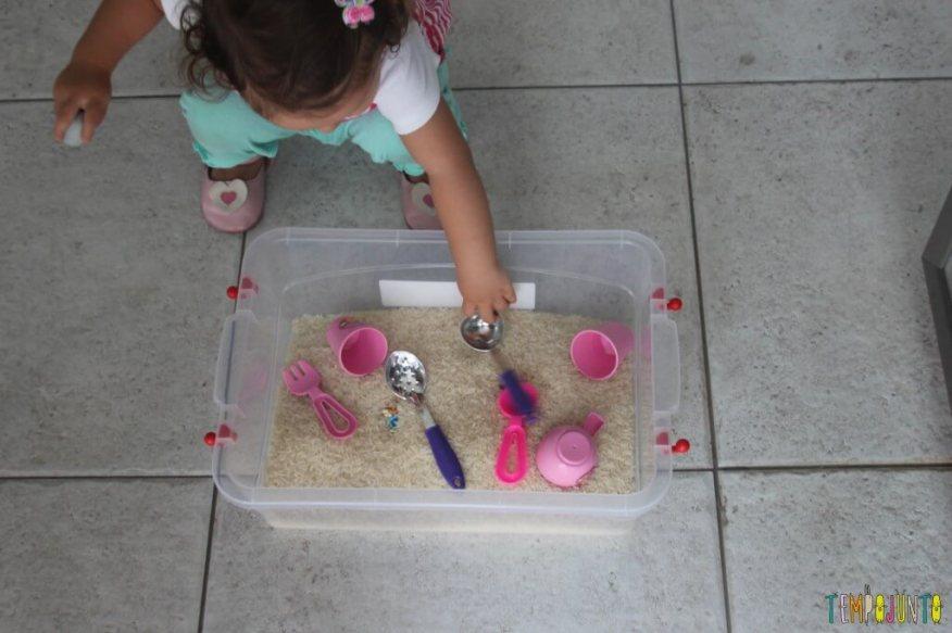 Brincadeira sensorial com arroz para bebês - começando a mexer na caixa