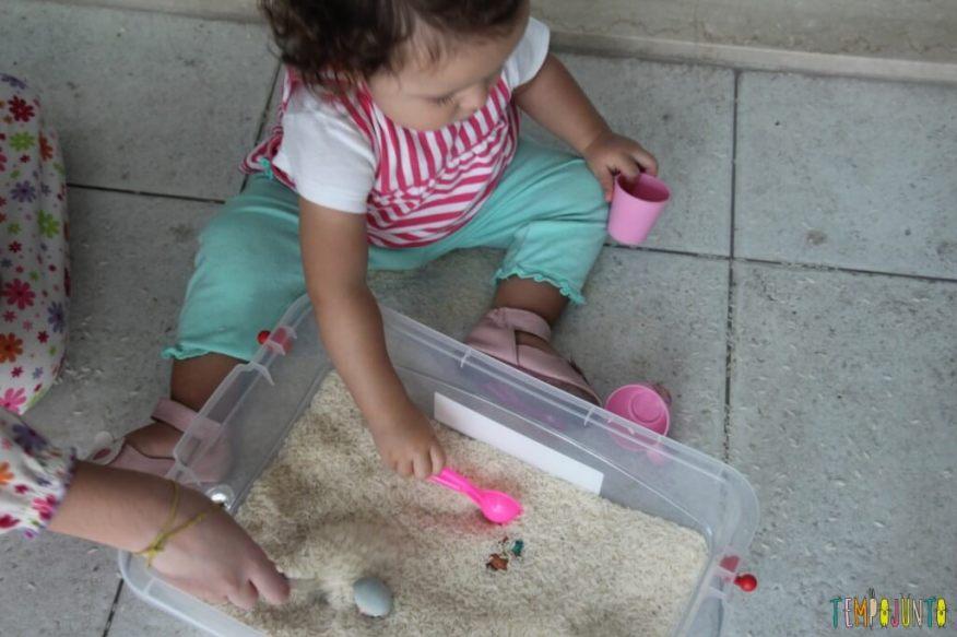 Brincadeira sensorial com arroz para bebês - enchendo a colher de arroz