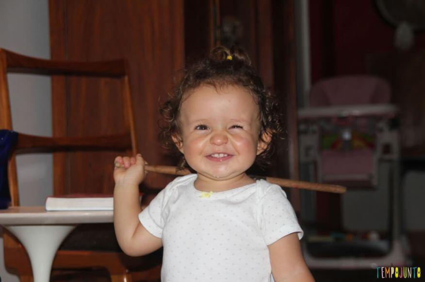 O brincar livre de um bebê - baqueta na mao
