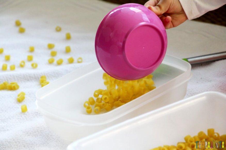 Brincadeira para fazer em casa com o seu filho pequeno - derrubando o macarrao de um pote para o outro