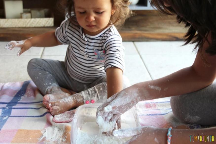 Brincadeira sensorial para todas as idades_maisena_gabi experimentando farinha e agua com a mao