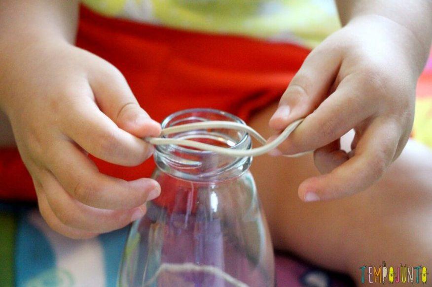 Como estimular a coordenação motora dos bebês - gabi encaixando o elastico na garrafa estreita