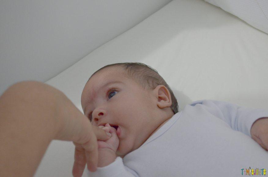Usar suas mãos para brincar com o recém-nascido - bebe mordendo o dedo da mar