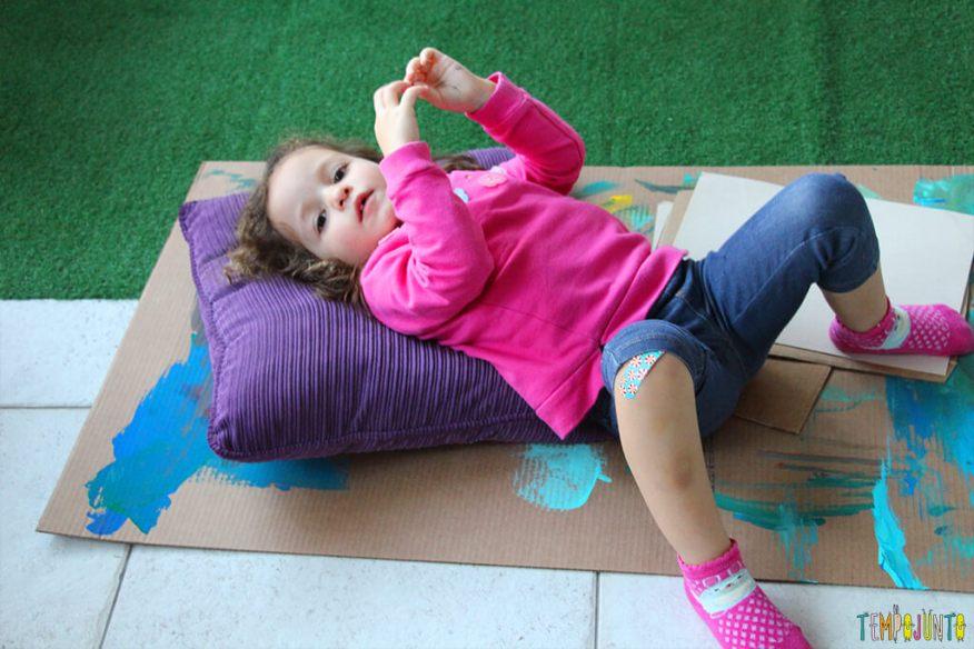 Atividade de artes para estimular a brincadeira de imaginação - gabi deitada no tapete